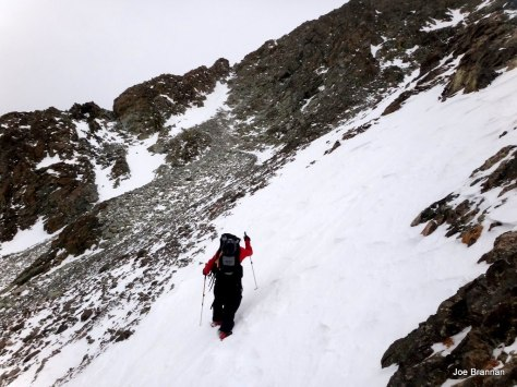 Traversing snow slopes to the base of the N. Couloir